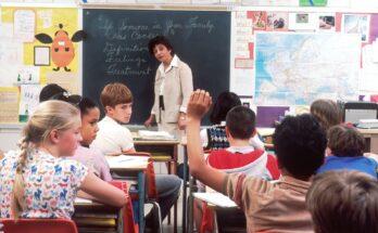 Kind steekt hand op in klas om iets te vragen
